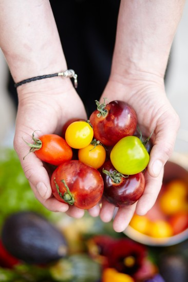 Chef Nicol Roarke holds heirloom tomatoes in her hands.